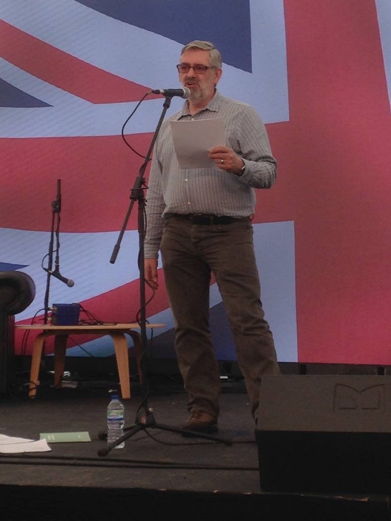 Picture of Seamus reading with a large Union Jack projected in the background